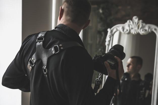 Retrato de um jovem fotógrafo elegante com sua câmera profissional no espelho