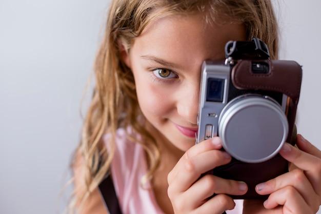Retrato de um jovem garoto lindo segurando uma câmera vintage e sorrindo. fundo branco. crianças dentro de casa. conceito de fotografia