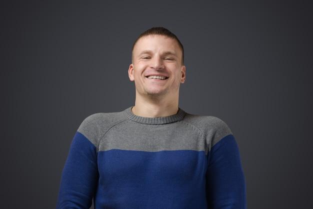 Retrato de um jovem gay que sorri. foto emocional em estúdio em uma superfície preta