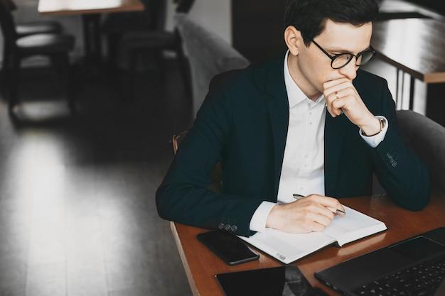 Retrato de um jovem gerente confiante, pensando enquanto bebe café e escrevendo em seu caderno enquanto está sentado em uma cafeteria.