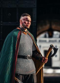 Retrato de um jovem guerreiro medieval em armadura com um machado nas mãos. no processo de batalha
