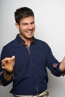Retrato de um jovem hispânico alegre, de camisa azul, posando contra uma parede branca