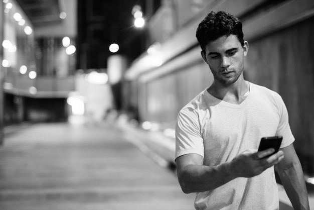 Retrato de um jovem hispânico explorando as ruas da cidade à noite