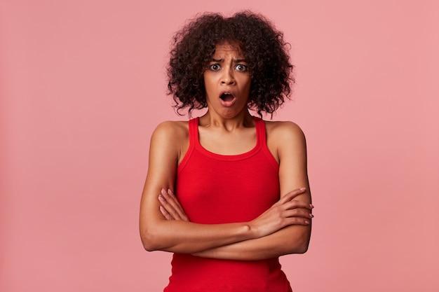 Retrato de um jovem homem afro-americano chocado, vestindo uma camiseta vermelha, com cabelos escuros encaracolados. olhando com os olhos bem abertos e a boca isolada.