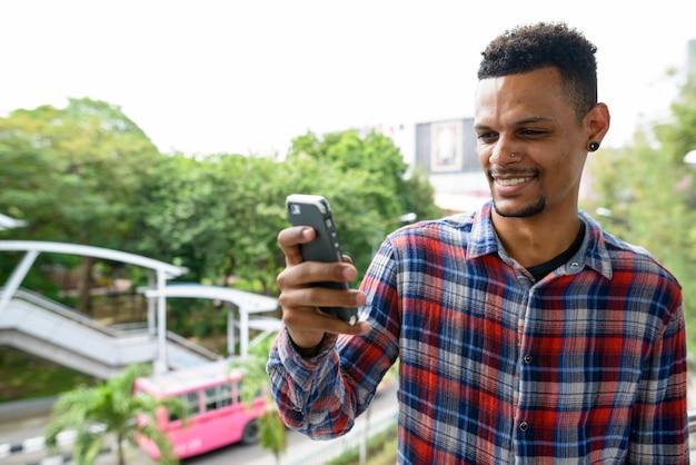 Retrato de um jovem homem barbudo hipster africano contra a vista das ruas da cidade ao ar livre