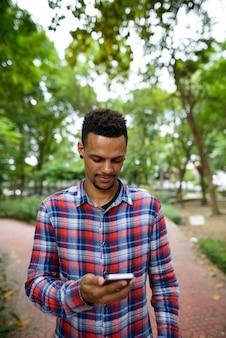 Retrato de um jovem homem barbudo hipster africano no parque ao ar livre
