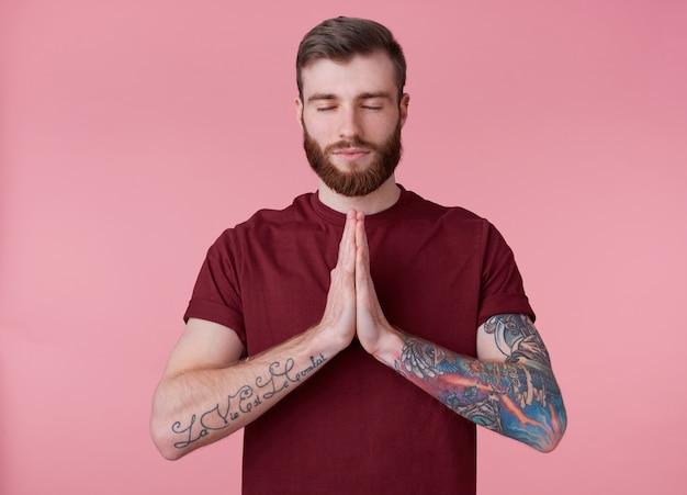 Retrato de um jovem homem barbudo vermelho atraente em t-shirt em branco, parece tranquilo e calmo, sorri, fica sobre um fundo rosa com os olhos fechados e mostrando o gesto de oração.