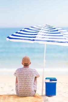 Retrato de um jovem homem de barba em uma praia sob o guarda-sol no verão