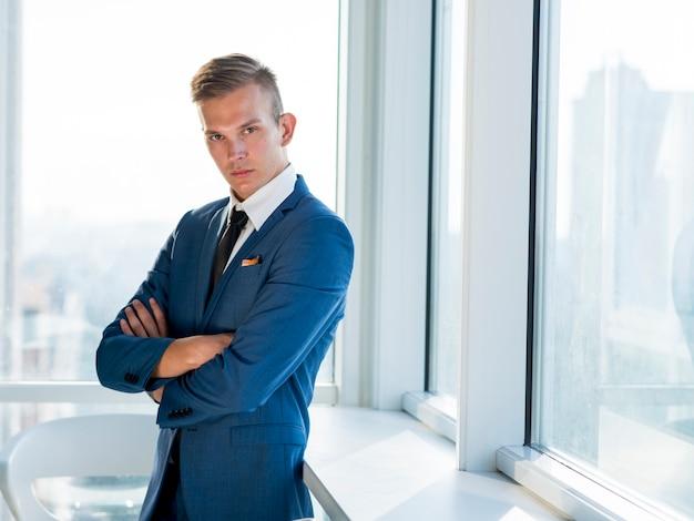 Retrato, de, um, jovem, homem negócios, com, braços dobrados