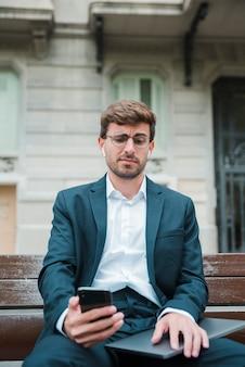 Retrato, de, um, jovem, homem negócios, videochamada, chamando, telefone móvel