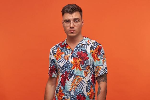 Retrato de um jovem homem pensante na camisa florida, fica sobre um fundo laranja com espaço de cópia e parece decidido.