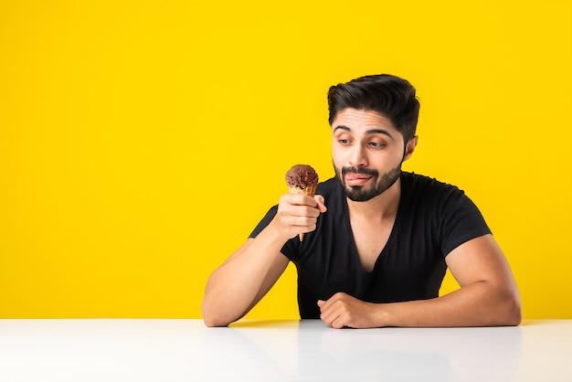 Retrato de um jovem indiano barbudo bonito comendo sorvete em casquinha ou picolé enquanto está sentado à mesa contra o fundo amarelo do estúdio