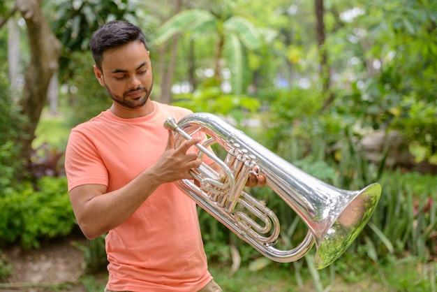 Retrato de um jovem indiano barbudo bonito tocando trompete no parque ao ar livre