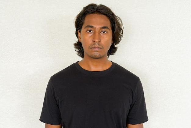Retrato de um jovem indiano bonito contra um fundo simples, filmado ao ar livre com luz natural