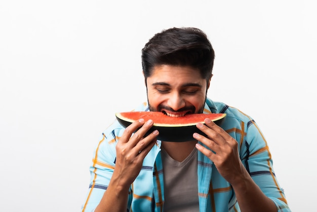 Retrato de um jovem indiano bonito sorrindo e comendo melancia fresca ou tarbooj enquanto está sentado à mesa ou isolado no chão de madeira