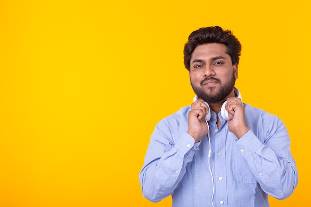 Retrato de um jovem indiano positivo com barba ouvindo um audiolivro na parede amarela