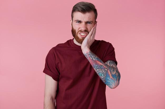 Retrato de um jovem infeliz barbudo com a mão tatuada, tocando a boca com a mão com uma expressão dolorosa por causa de uma dor de dente ou doença dentária nos dentes.