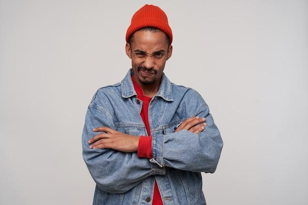 Retrato de um jovem insatisfeito, barbudo, moreno de pele escura, franzindo a testa e cruzando as mãos em pé no branco, usando um chapéu vermelho, uma blusa vermelha e um casaco jeans