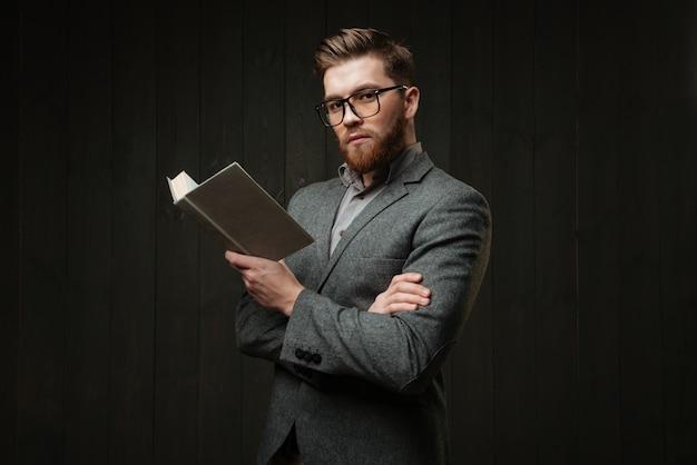 Retrato de um jovem inteligente em um terno casual em pé e segurando o livro isolado no fundo preto de madeira