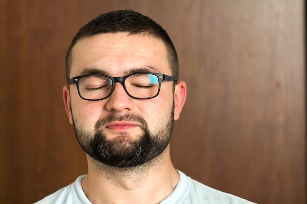 Retrato de um jovem inteligente moderno de cabelos pretos barbudo de óculos com cabelo curto e olhos negros gentis, sorrindo no fundo desfocado. conceito de juventude e confiança.