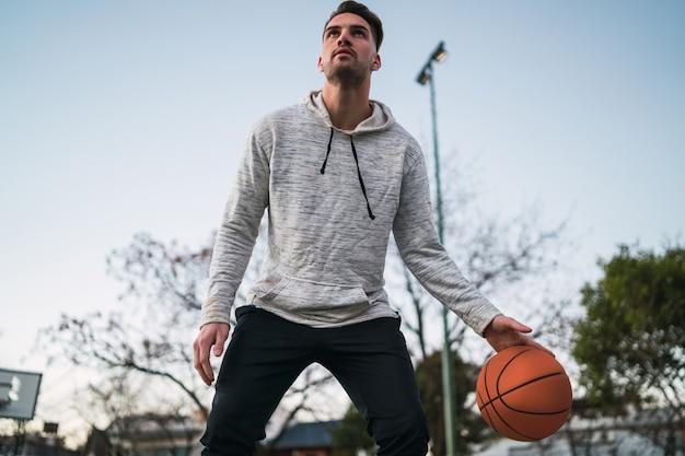 Retrato de um jovem jogador de basquete, jogando ao ar livre. conceito de esporte. conceito de basquete.