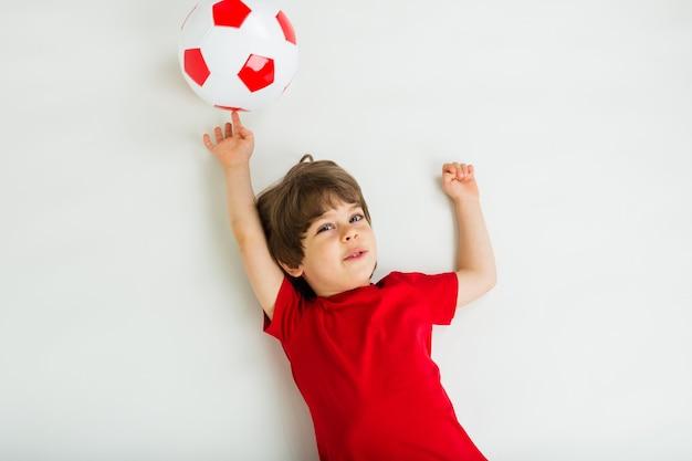 Retrato de um jovem jogador de futebol em uma camiseta vermelha deitado com uma bola de futebol vermelha e branca em uma superfície branca com espaço para texto. esportes para crianças