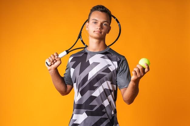 Retrato de um jovem jogador de tênis em fundo laranja close-up