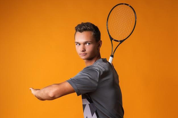 Retrato de um jovem jogador de tênis em fundo laranja