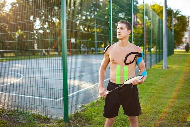 Retrato de um jovem jogador de tênis profissional caucasiano com fitas elásticas no corpo carregando uma raquete perto de um campo de esportes cercado