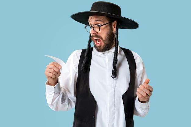 Retrato de um jovem judeu ortodoxo com boleto de aposta no estúdio. férias, celebração, judaísmo, conceito de apostas.