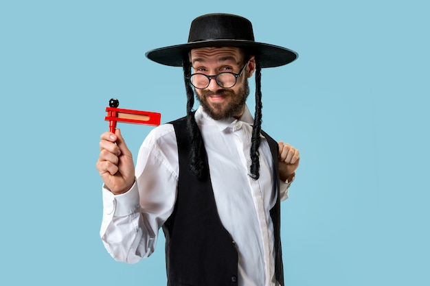 Retrato de um jovem judeu ortodoxo com catraca de madeira grager durante o festival de purim. férias, celebração, judaísmo, tradição, conceito de religião.