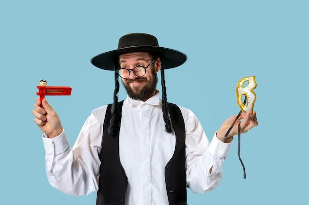 Retrato de um jovem judeu ortodoxo com catraca de madeira grager durante o festival de purim.
