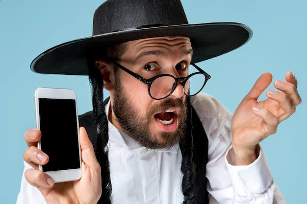 Retrato de um jovem judeu ortodoxo com telefone celular no estúdio. purim, negócios, empresário, festival, feriado, celebração, judaísmo, conceito de religião.