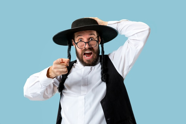 Retrato de um jovem judeu ortodoxo durante o festival de purim. férias, celebração, judaísmo, conceito de religião. emoções humanas Foto gratuita