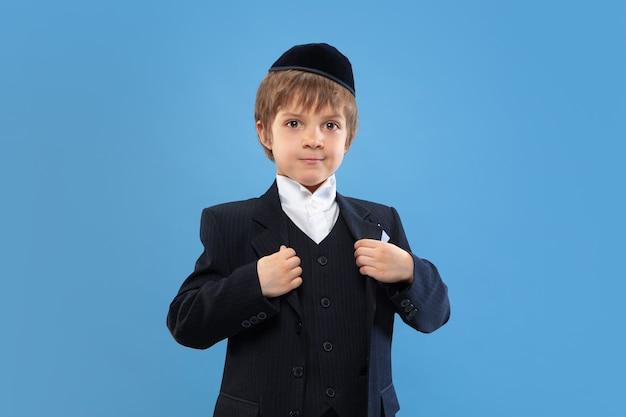 Retrato de um jovem judeu ortodoxo isolado no estúdio azul
