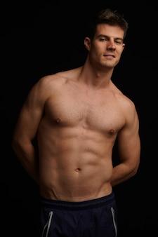Retrato de um jovem latino-americano, atlético, sem camisa, posando contra uma parede preta