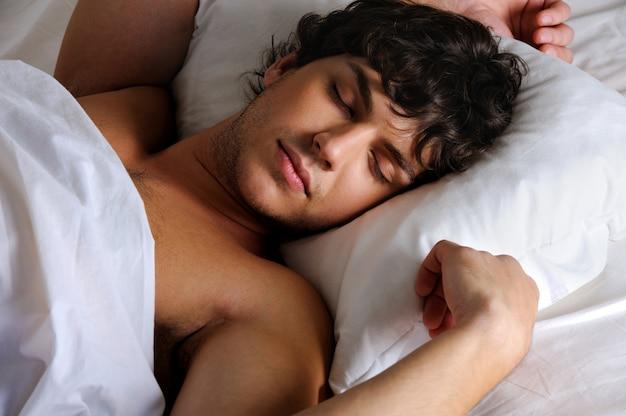 Retrato de um jovem lindo dormindo doce, deitado de costas