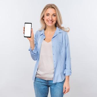 Retrato, de, um, jovem, loiro, mulher olha, câmera, mostrando, telefone móvel, com, em branco, tela branca