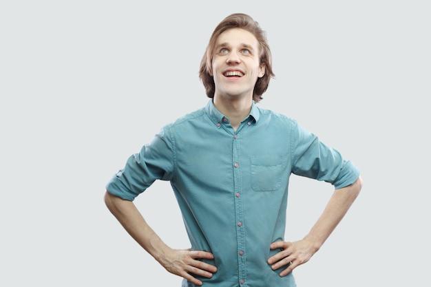 Retrato de um jovem louro bonito de cabelos compridos sonhador feliz na camisa azul casual em pé com as mãos na cintura e olhando para longe e a sonhar. tiro de estúdio interno, isolado em fundo cinza claro.