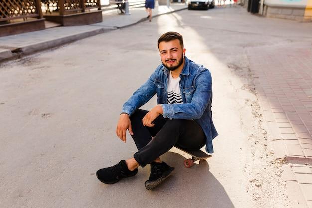 Retrato, de, um, jovem, macho, skateboarder, sentando, ligado, skateboard