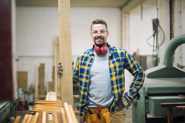 Retrato de um jovem marceneiro segurando madeira em sua oficina de carpintaria