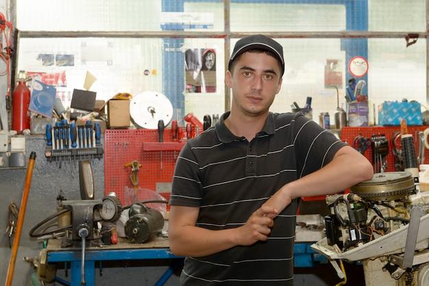 Retrato de um jovem mecânico em sua oficina