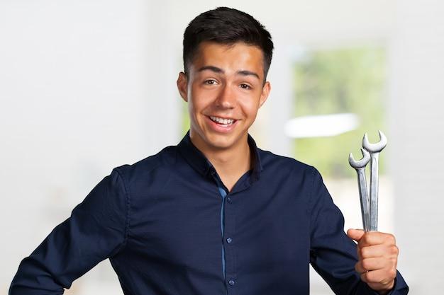 Retrato de um jovem mecânico segurando uma chave