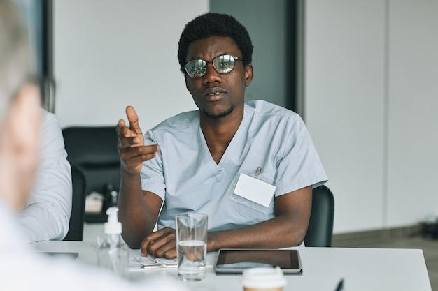 Retrato de um jovem médico afro-americano falando com colegas durante uma reunião médica na sala de conferências
