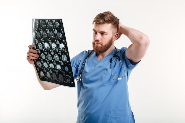 Retrato de um jovem médico analisando uma tomografia computadorizada