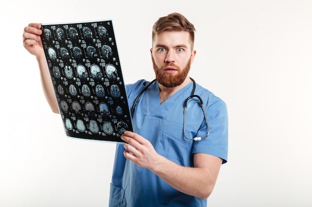 Retrato de um jovem médico chocado segurando a tomografia computadorizada
