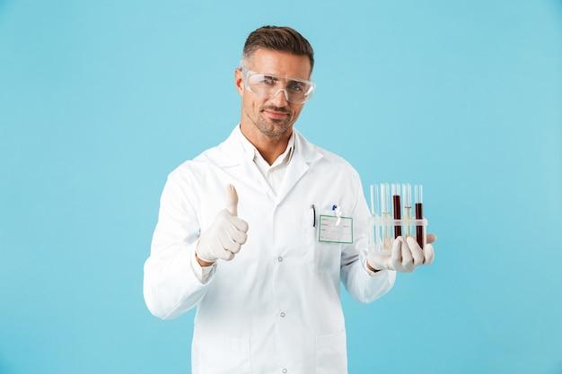 Retrato de um jovem médico de óculos segurando tubos de ensaio com sangue, isolado sobre a parede azul