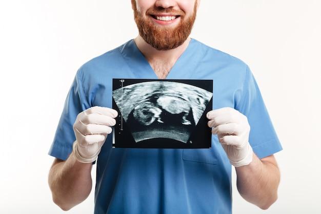 Retrato de um jovem médico masculino sorridente, mostrando radiografia