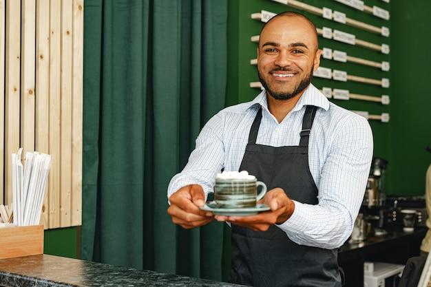 Retrato de um jovem mestiço barista em uma cafeteria
