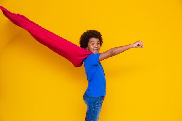 Retrato de um jovem mestiço vestido de super-herói. bebê preto fantasiado de super-herói. o conceito de vencedor e sucesso.